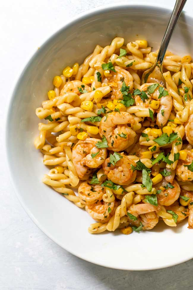 Cilantro-butter shrimp pasta in a bowl with a fork