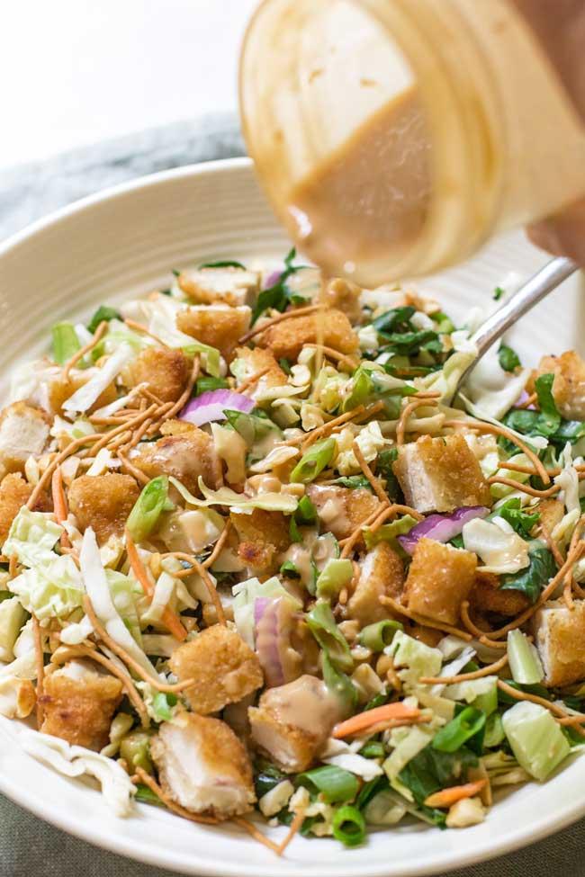 pouring peanut-garlic dressing on the crispy chicken salad