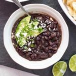 overhead photo of a bowl of black bean soup garnished with cilantro and avocado
