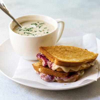 photo of a turkey grilled cheese on a plate with a bowl of cauliflower soup