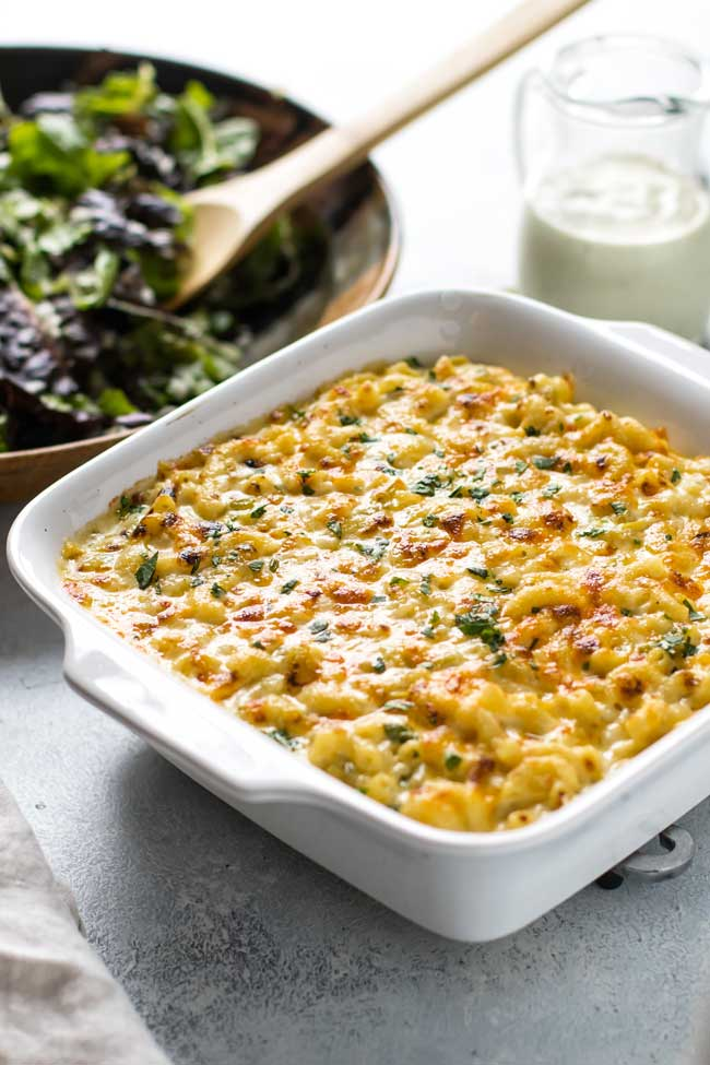 photo of green chile macaroni and cheese in a baking dish with a salad in the background