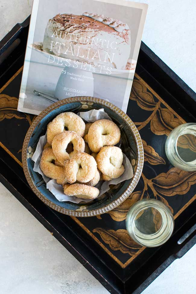 overhead photo of a tray with cookies, glasses of wine, and a cookbook
