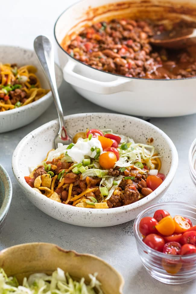 photo of a bowl of frito pie with bowls of toppings around it