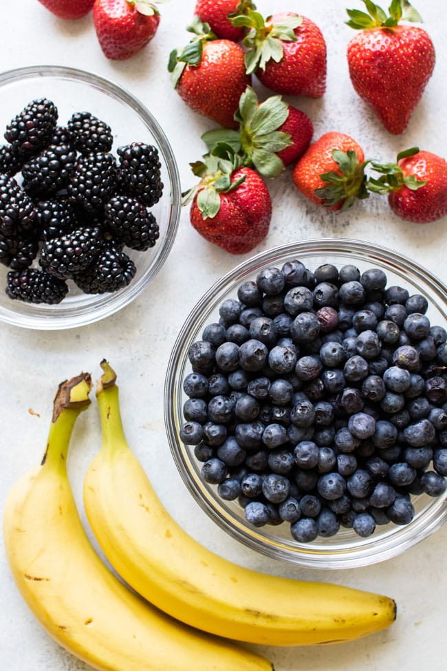 overhead photo of bananas, strawberries, blackberries, blueberries on a board