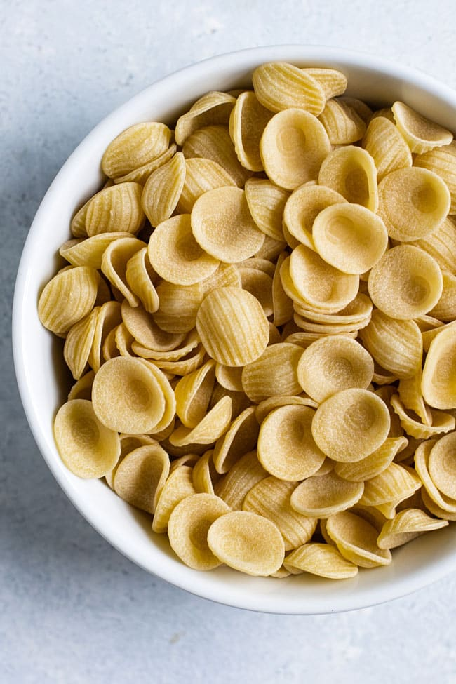 Overhead photo of a bowl of uncokked orecchiette pasta