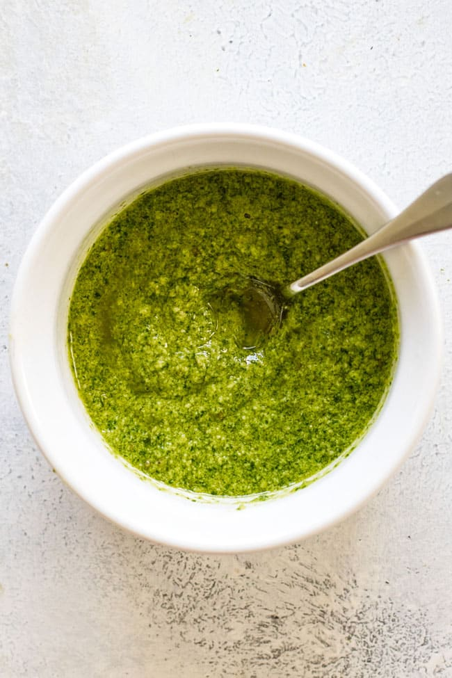 overhead photo of a bowl of pesto with a spoon