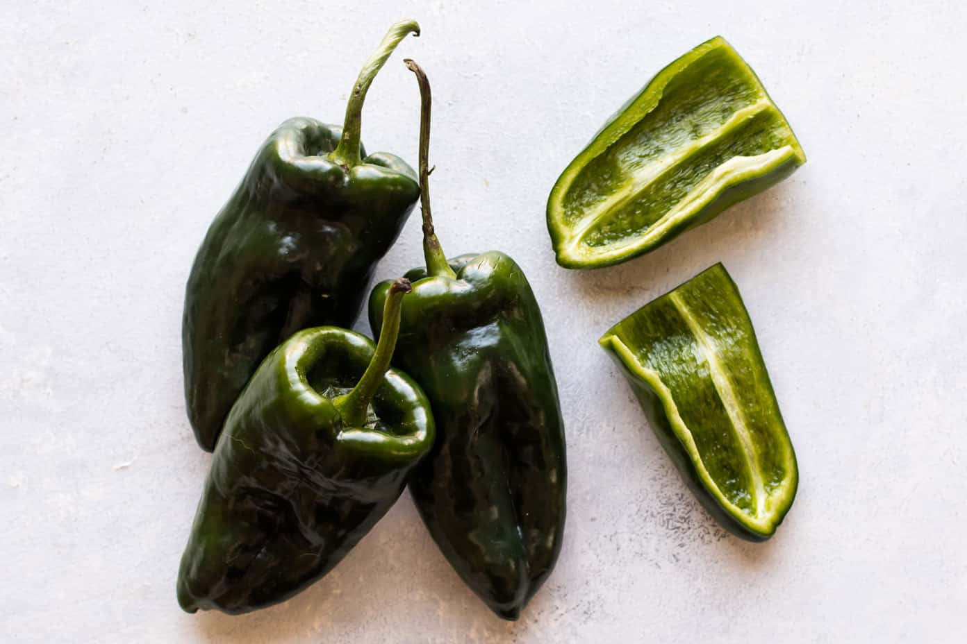 photo of three poblano peppers and one sliced in half