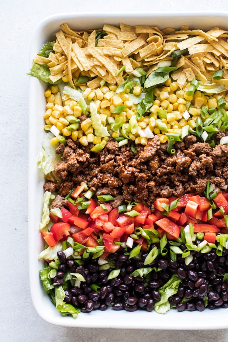 overhead photo of a taco salad with beans, peppers, corn, tortilla strips, ground beef and lettuce