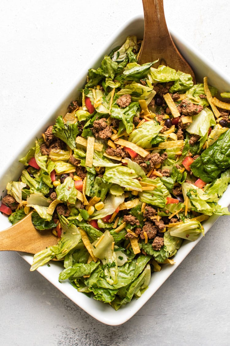 overhead photo of a tossed taco salad in a white dish