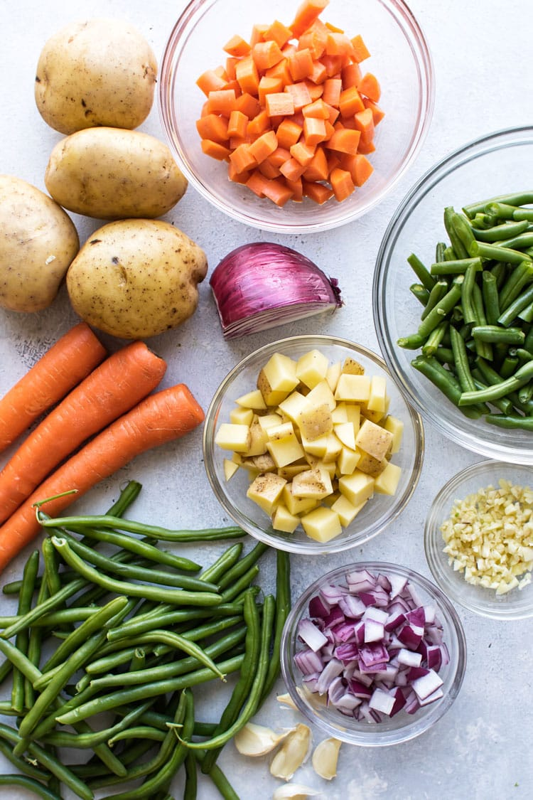 overhead photo of potatoes, carrots, onions, green beans chopped in bowls and whole