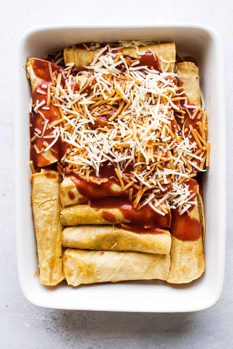 overhead photo of the enchiladas in a pan being topped with sauce and cheese