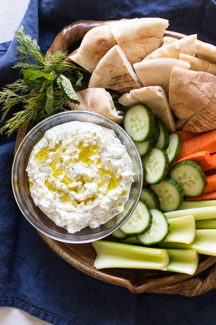 overhead photo of a bowl of tzatziki with pita and vegetables