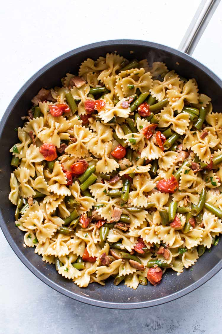 overhead photo of a skillet of pasta with bacon, green beans and tomatoes