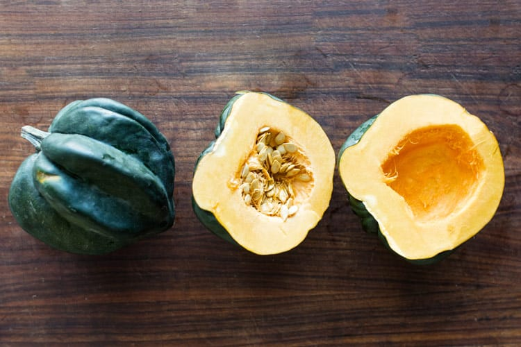 photo of a whole acorn squash, one half with seeds, and one half with seeds removed