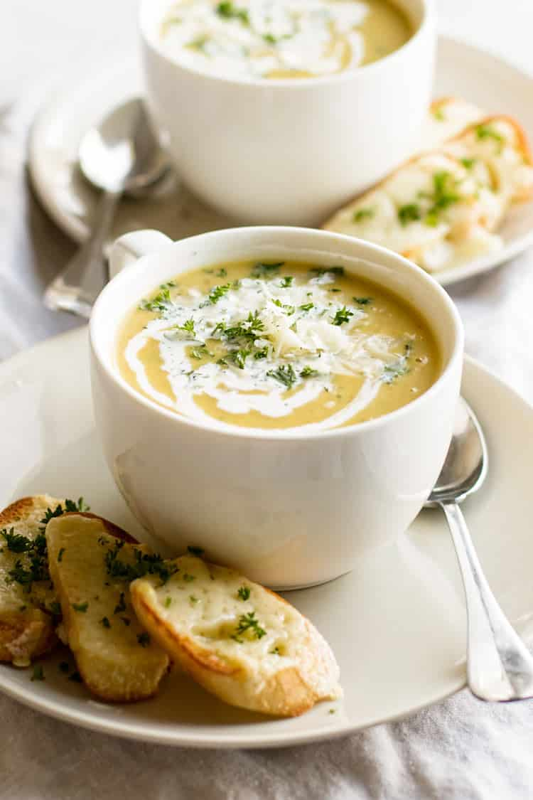 photo of a bowl of soup on a plate with gruyere toasts