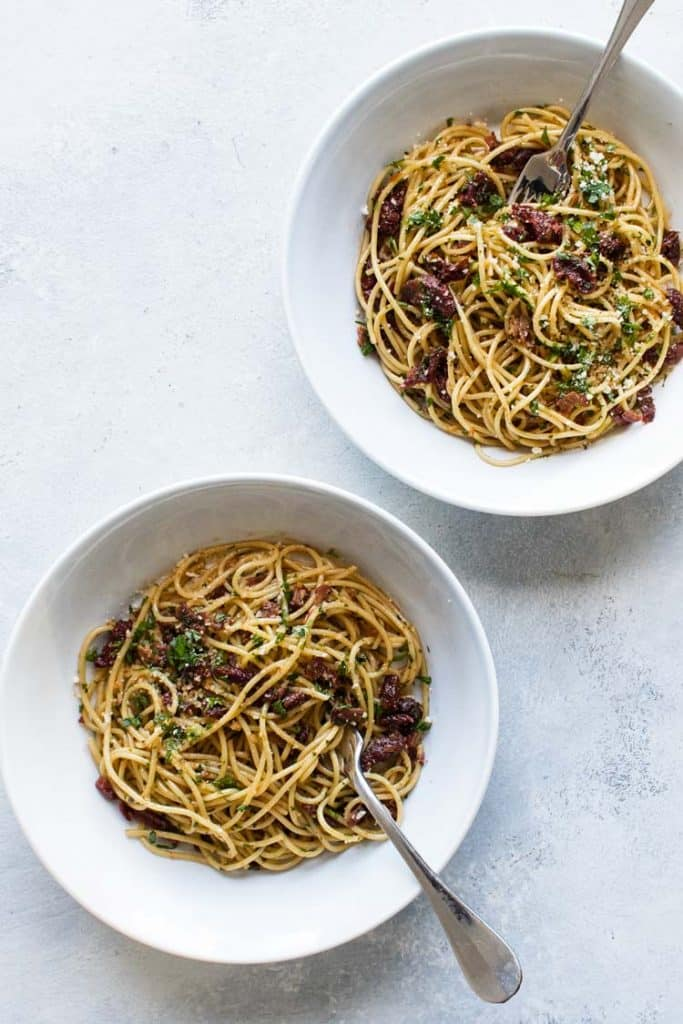 overhead photo of two bowls of spaghetti with sun-dried tomatoes and bacon