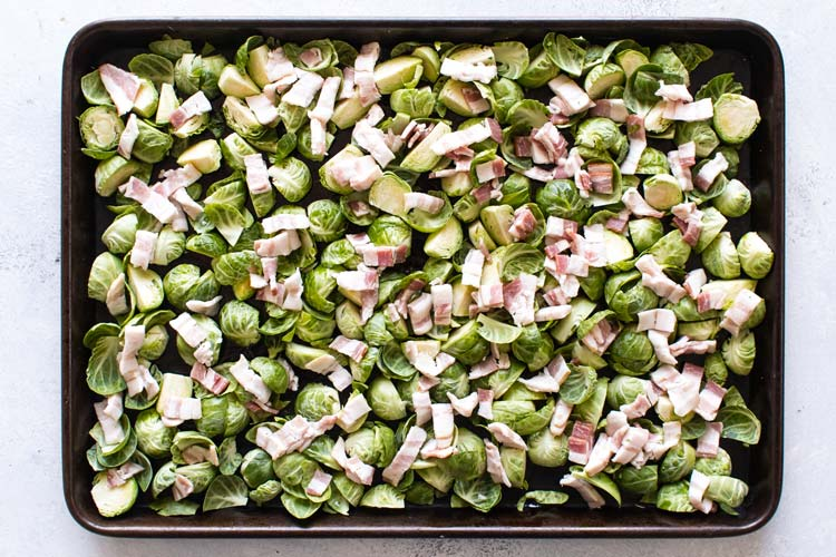 overhead photo of the raw sprouts and bacon scattered on a sheet pan