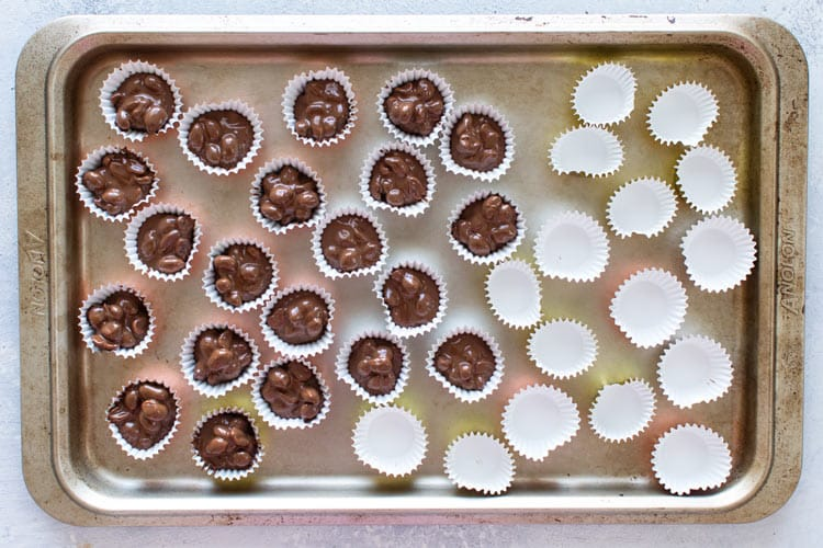 overhead photo showing some mini muffin cups filled with the melted chocolate and some empty