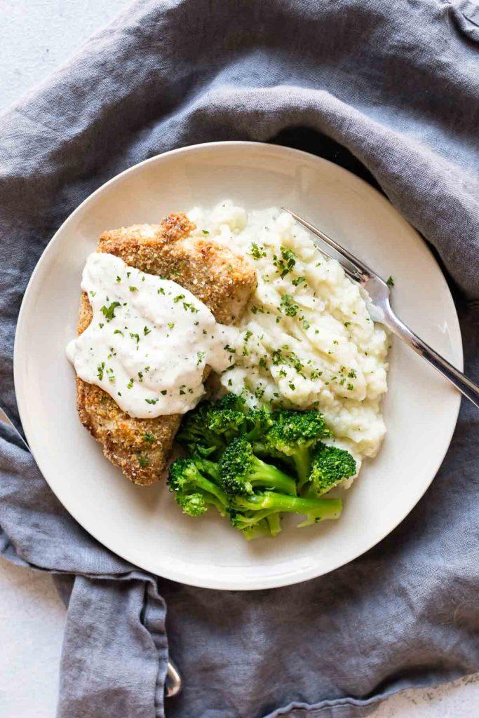 overhead photo of whole pork chop with sauce, broccoli and cauliflower mash