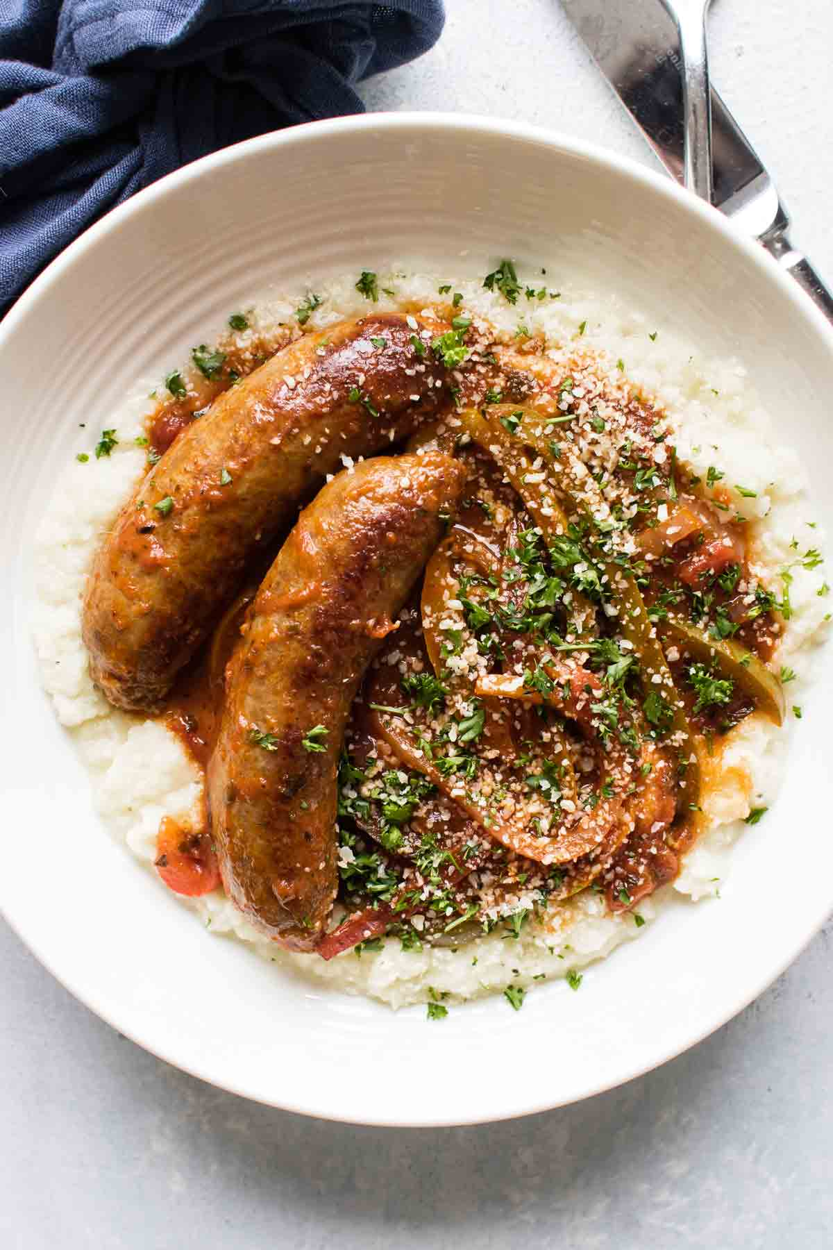 overehead photo of sausage and peppers in a bowl with parsley and parmesan