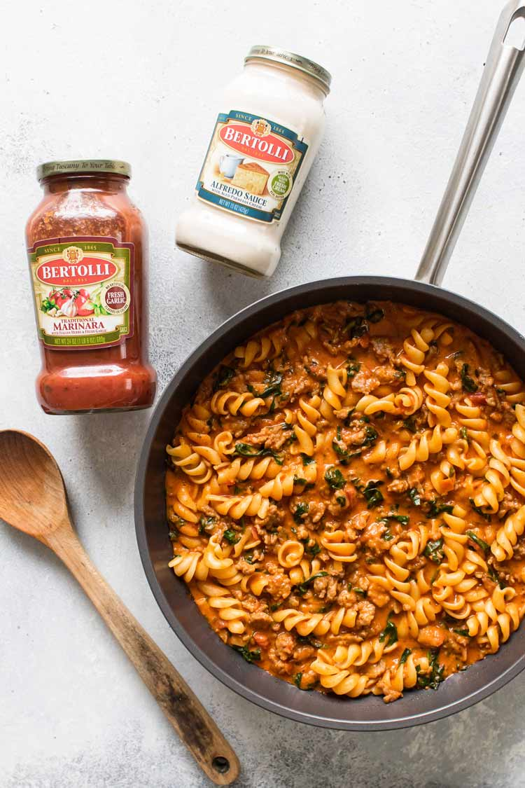 overhead photo of a skillet of pasta with two jars of sauce and a wooden spoon