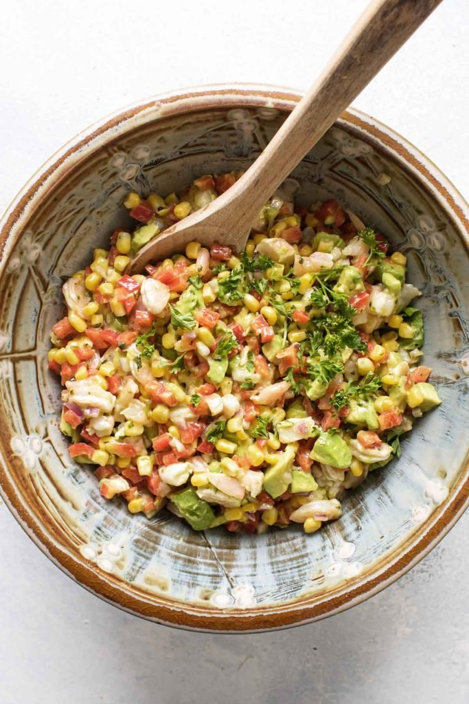photo of a bowl of salad with a wooden spoon