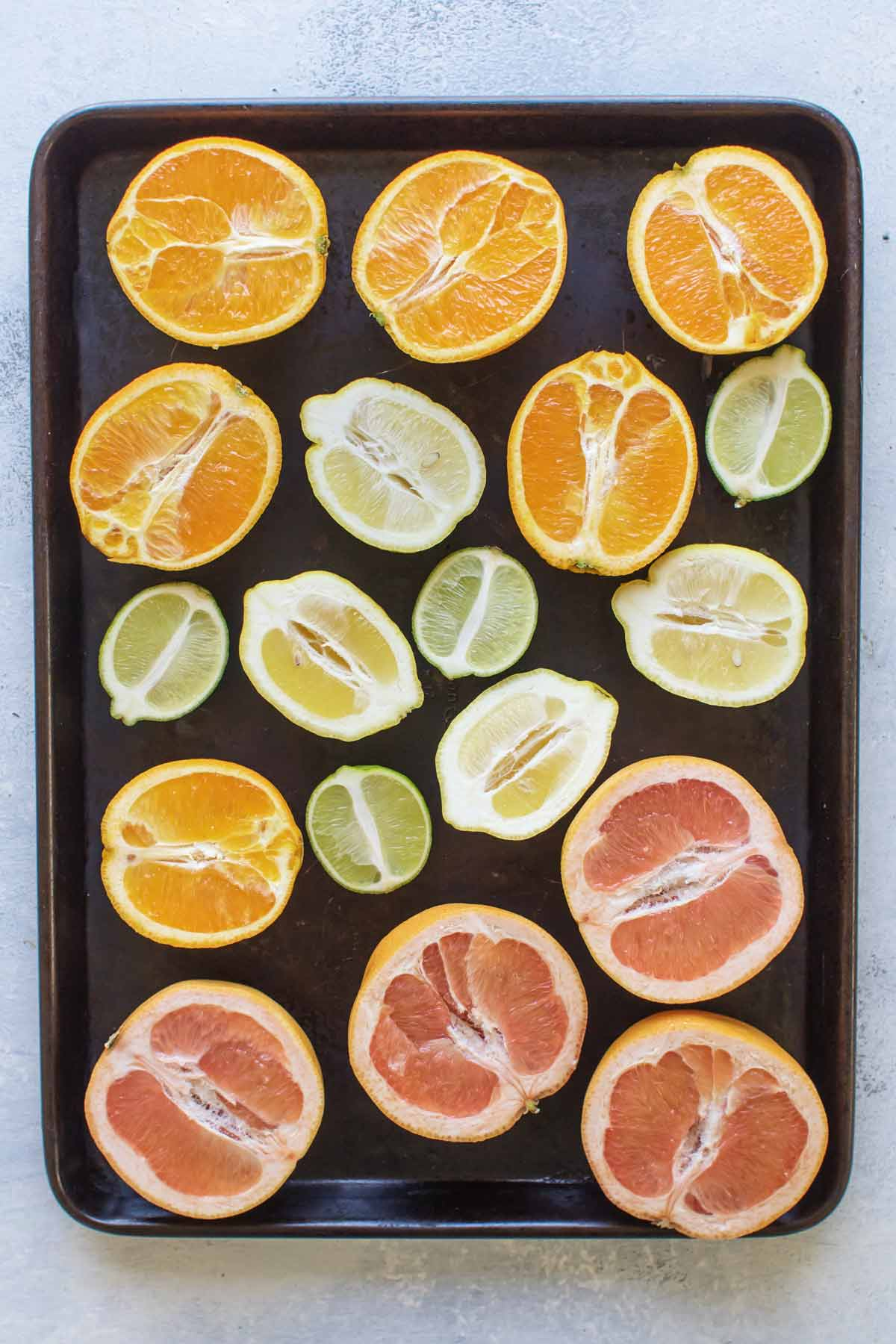 overhead photo of orange, lemon, lime, and grapefruit halves on a baking sheet