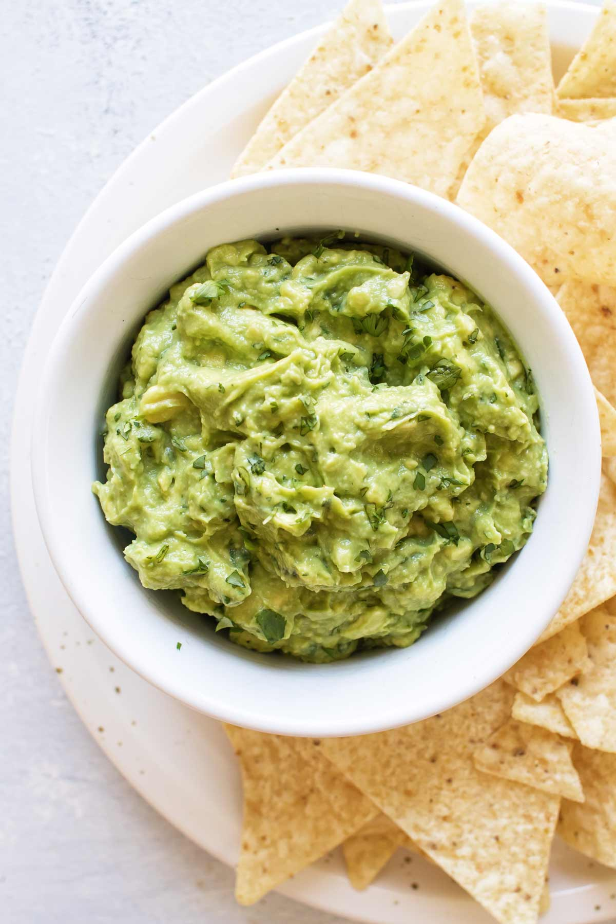 overhead photo of a bowl of guacamole on a plate with chips