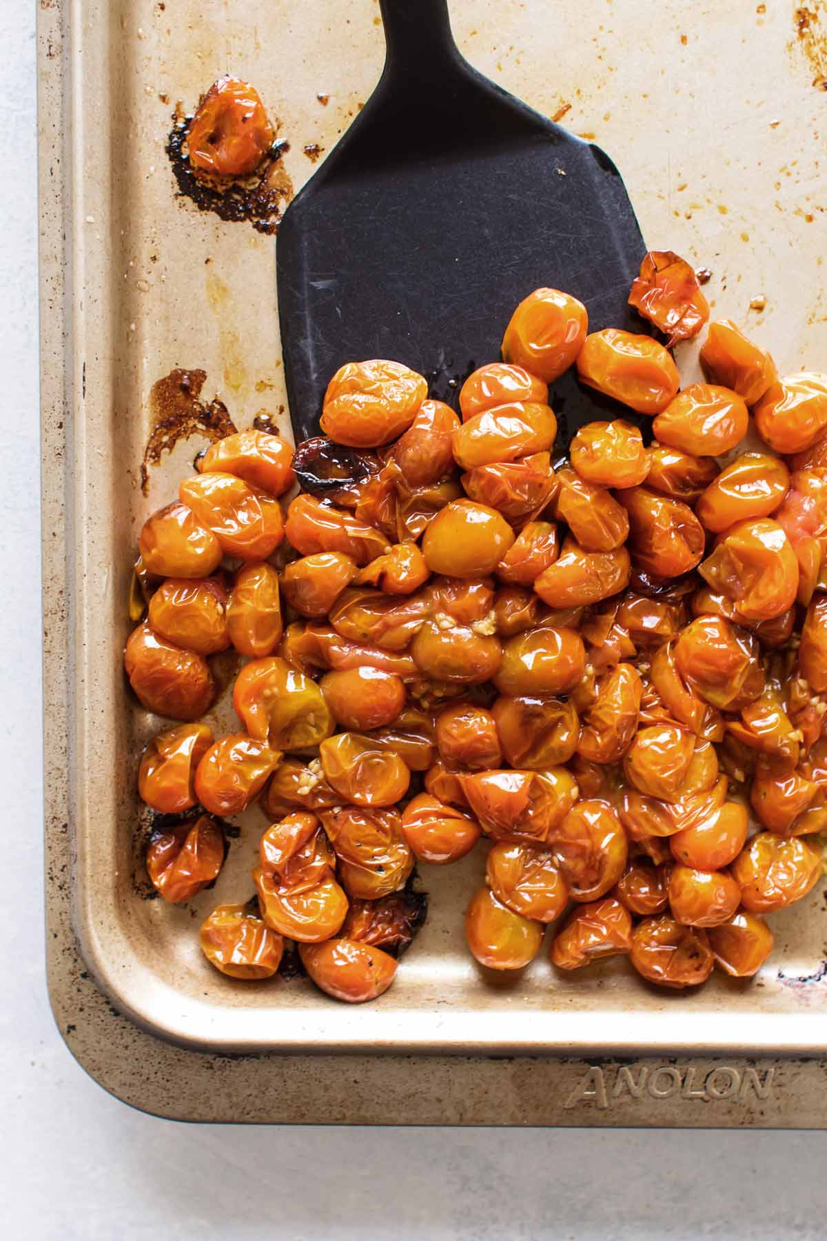 overhead photo of roasted tomatoes on a sheet pan