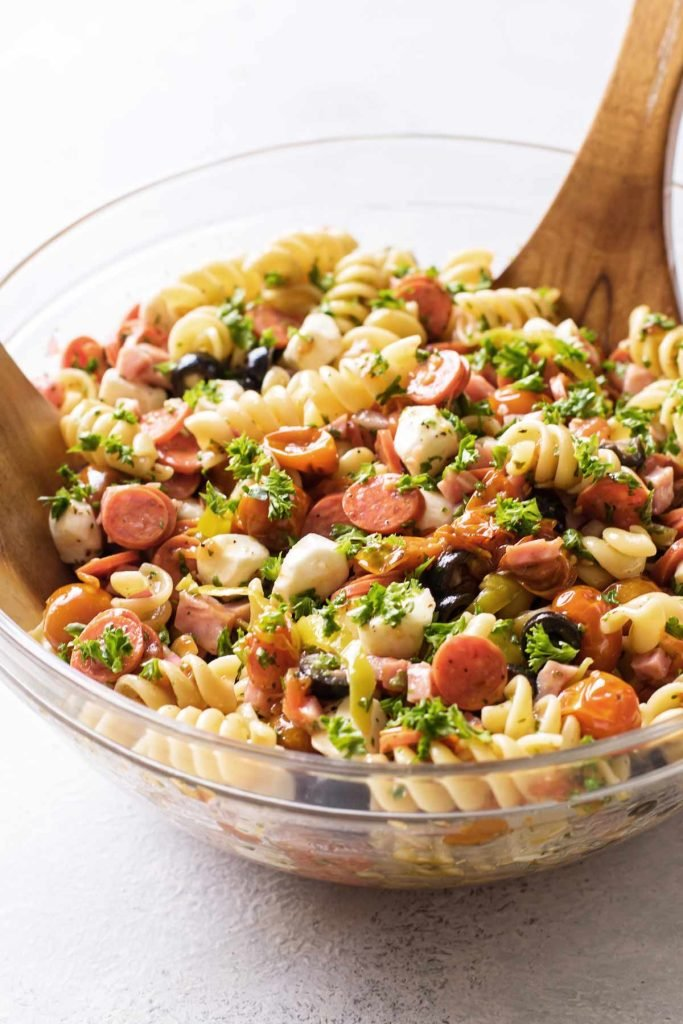 pasta salad in a clear glass serving bowl