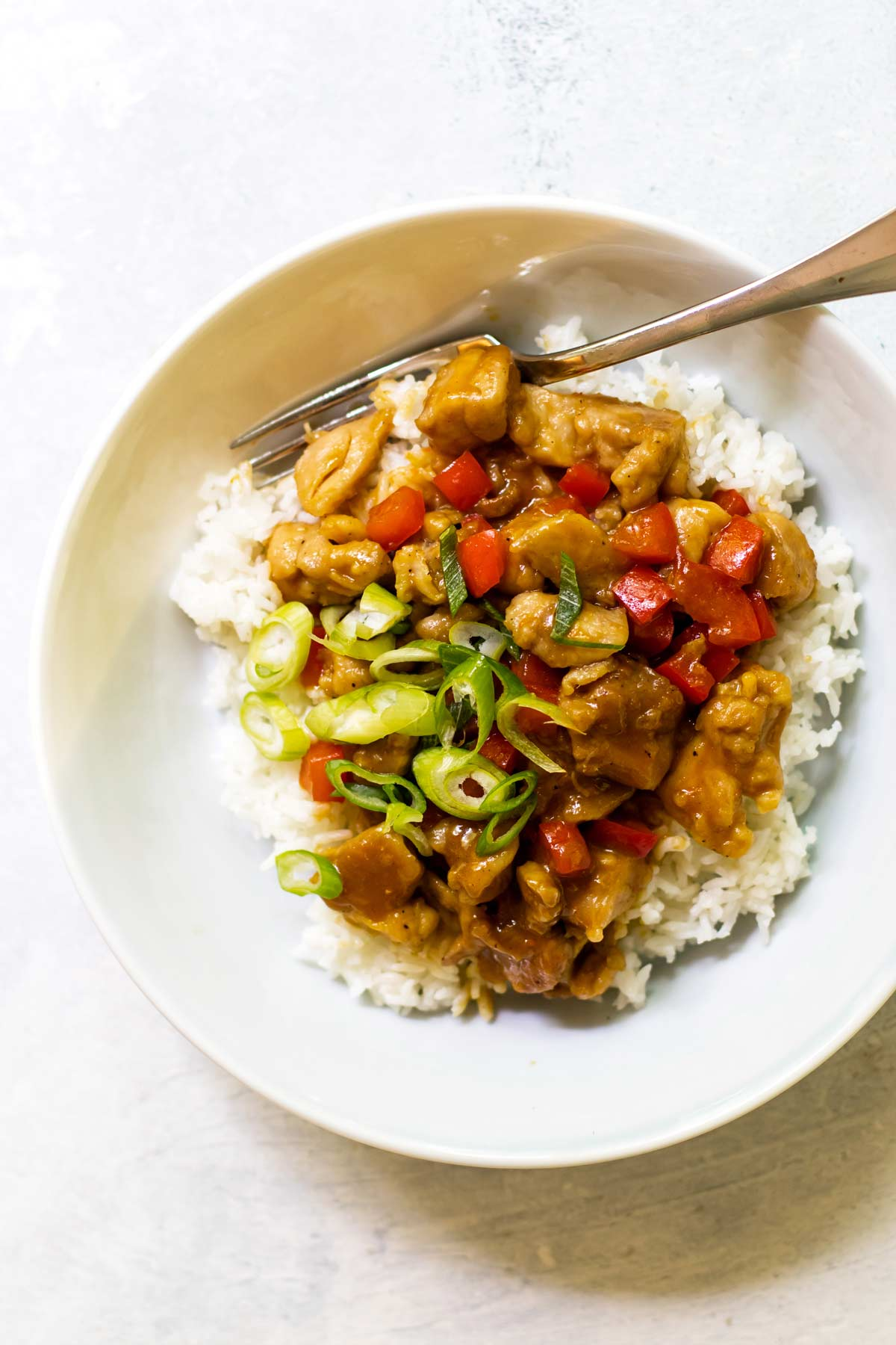 overehead photo of orange chicken in a bowl with rice