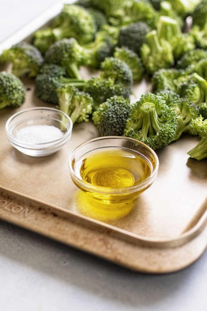 photo of a small bowl of oil and salt on a baking sheet with raw broccoli
