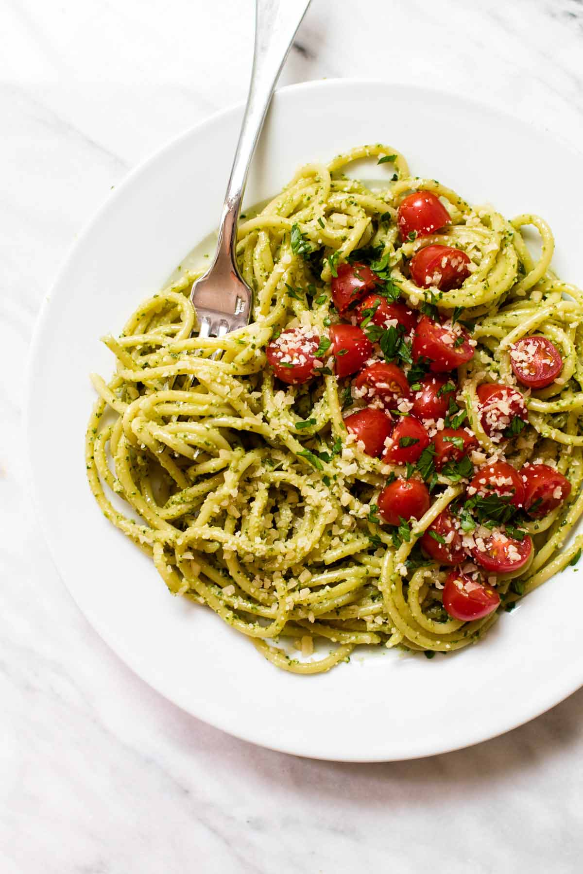 overhead photo of a plate of pasta with pesto and fresh tomatoes