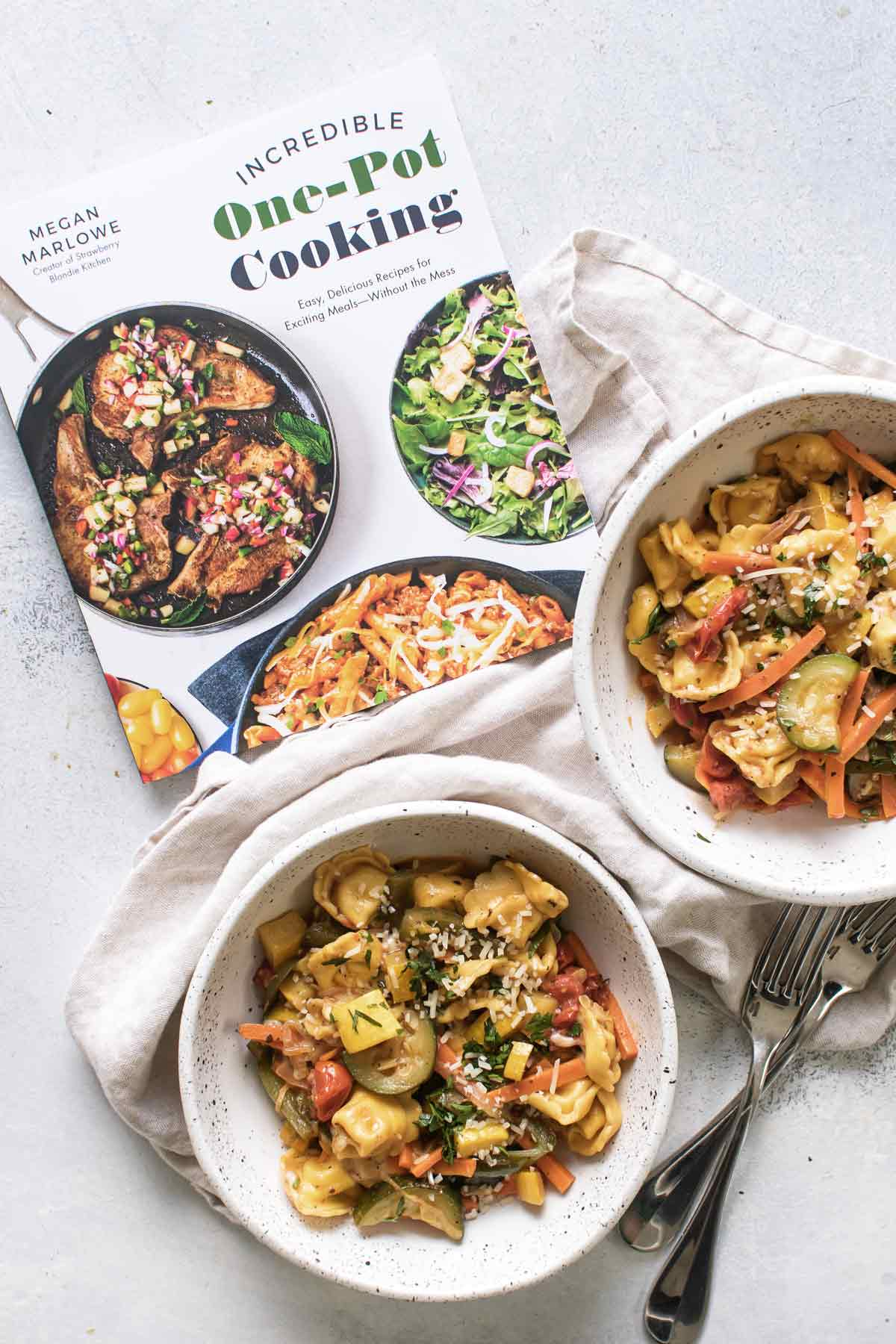 overhead photo of the cookbook with two bowls of pasta