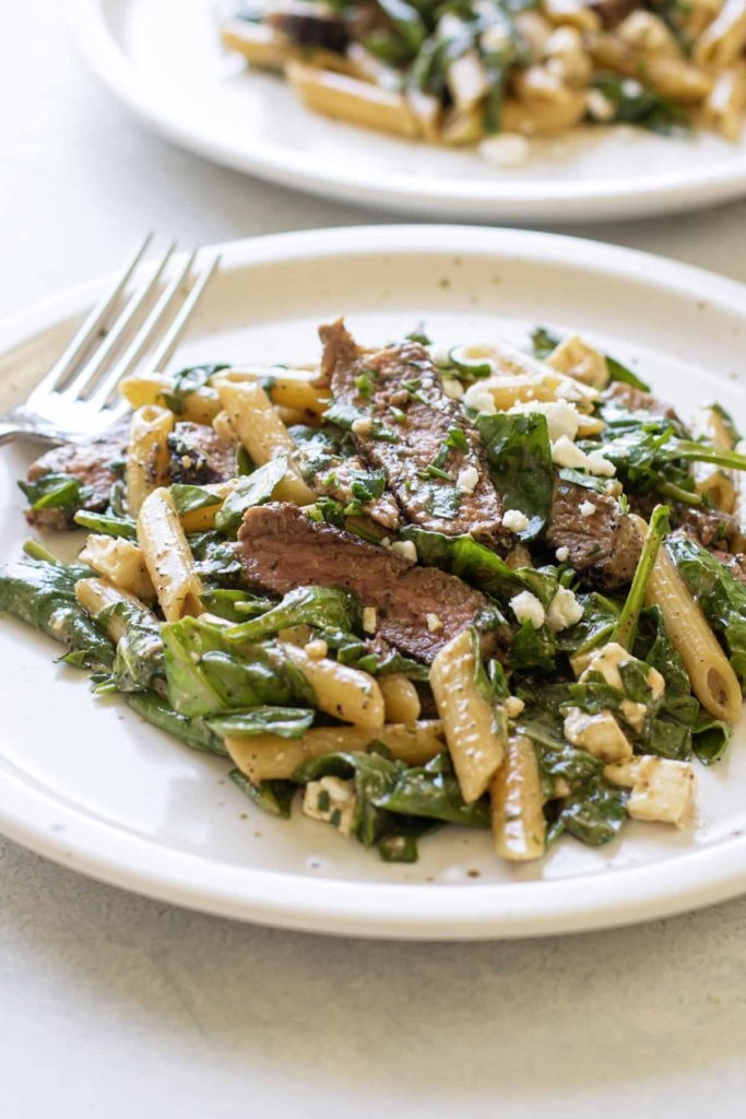 photo of a plate of steak and pasta