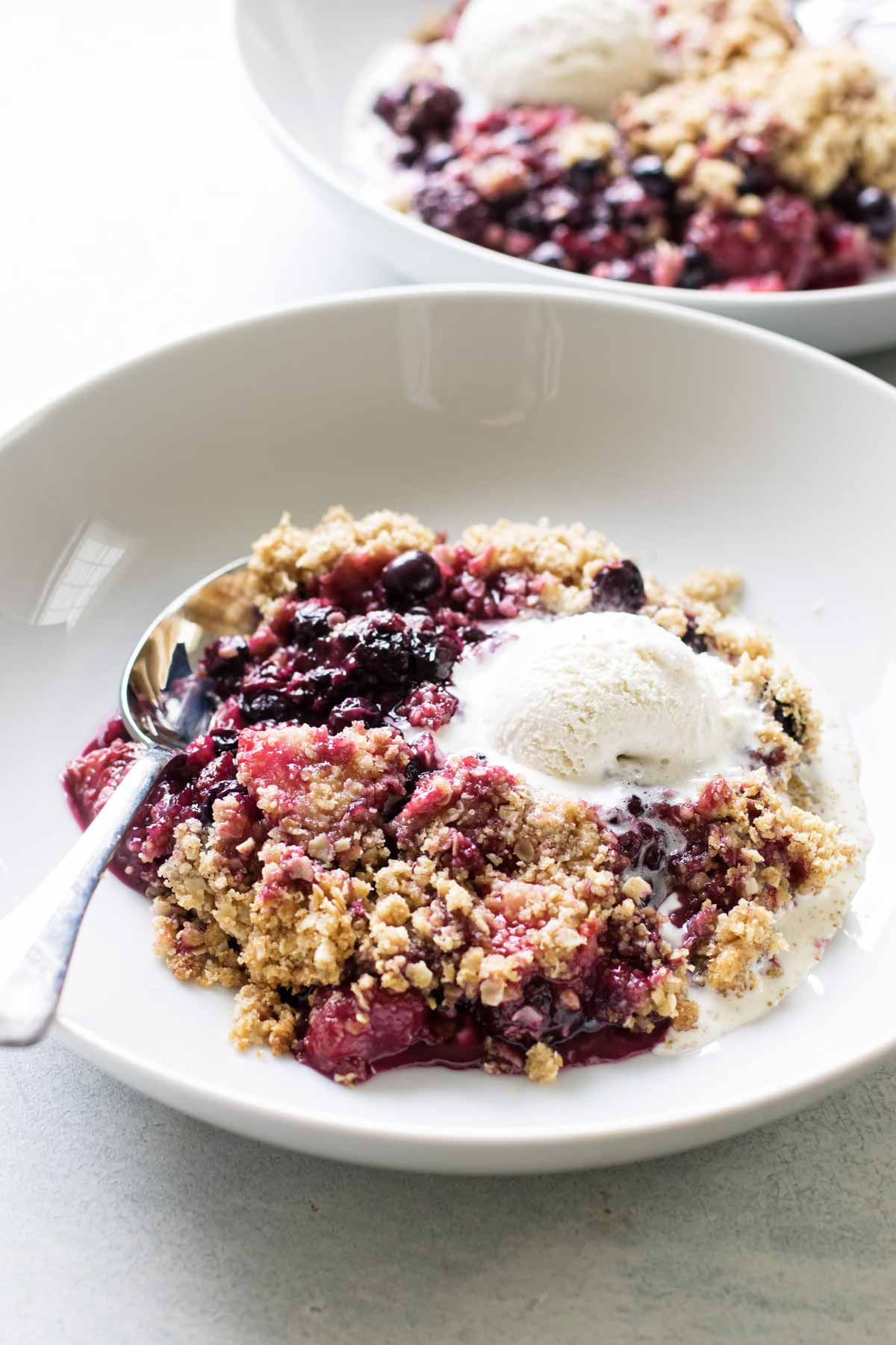 photo of a serving of berry crumble in a bowl with ice cream