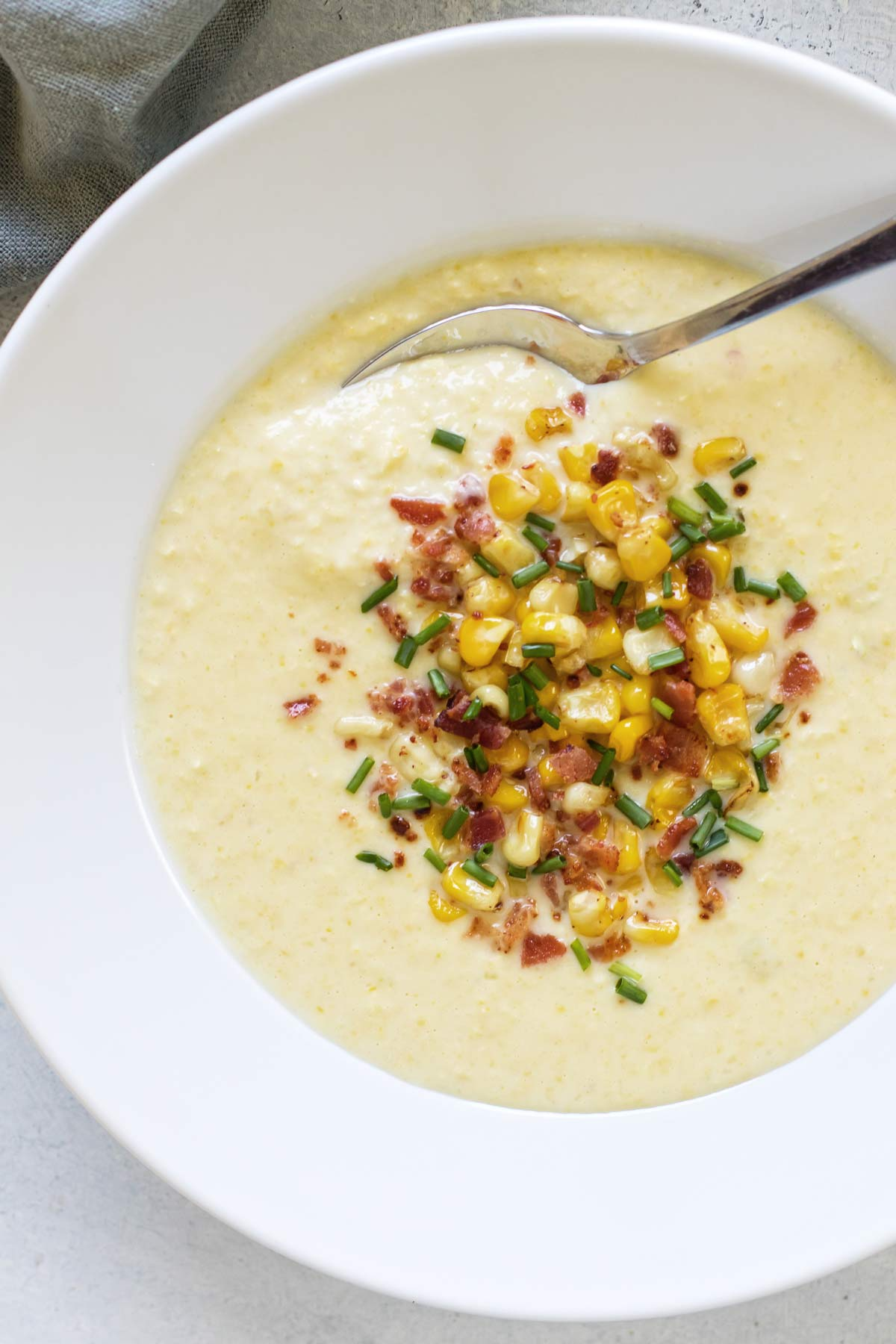 overhead photo of a bowl of corn soup with a spoon