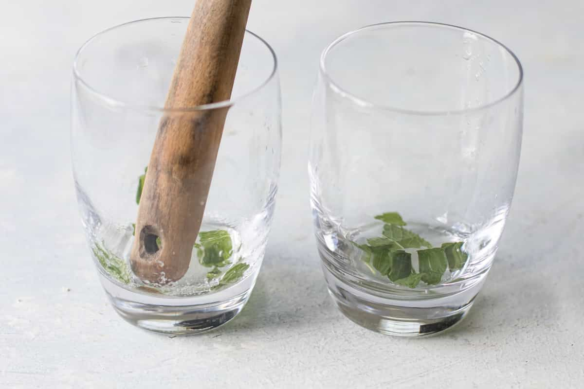 photo showing the mint and sugar being muddled in a glass