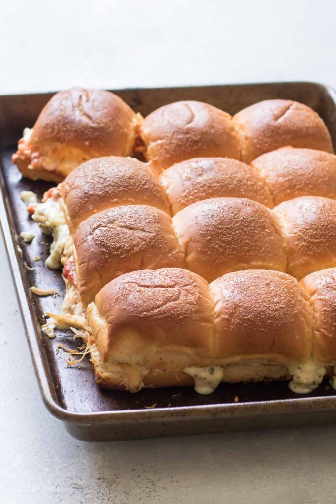 baked chicken sliders on a baking sheet.
