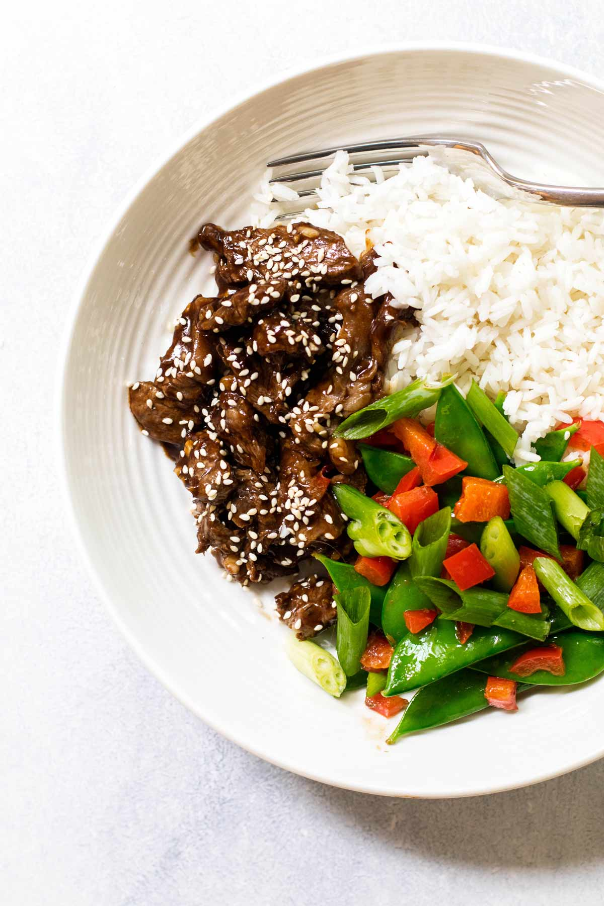 photo of a a bowl of sesame beef with rice and veggies.
