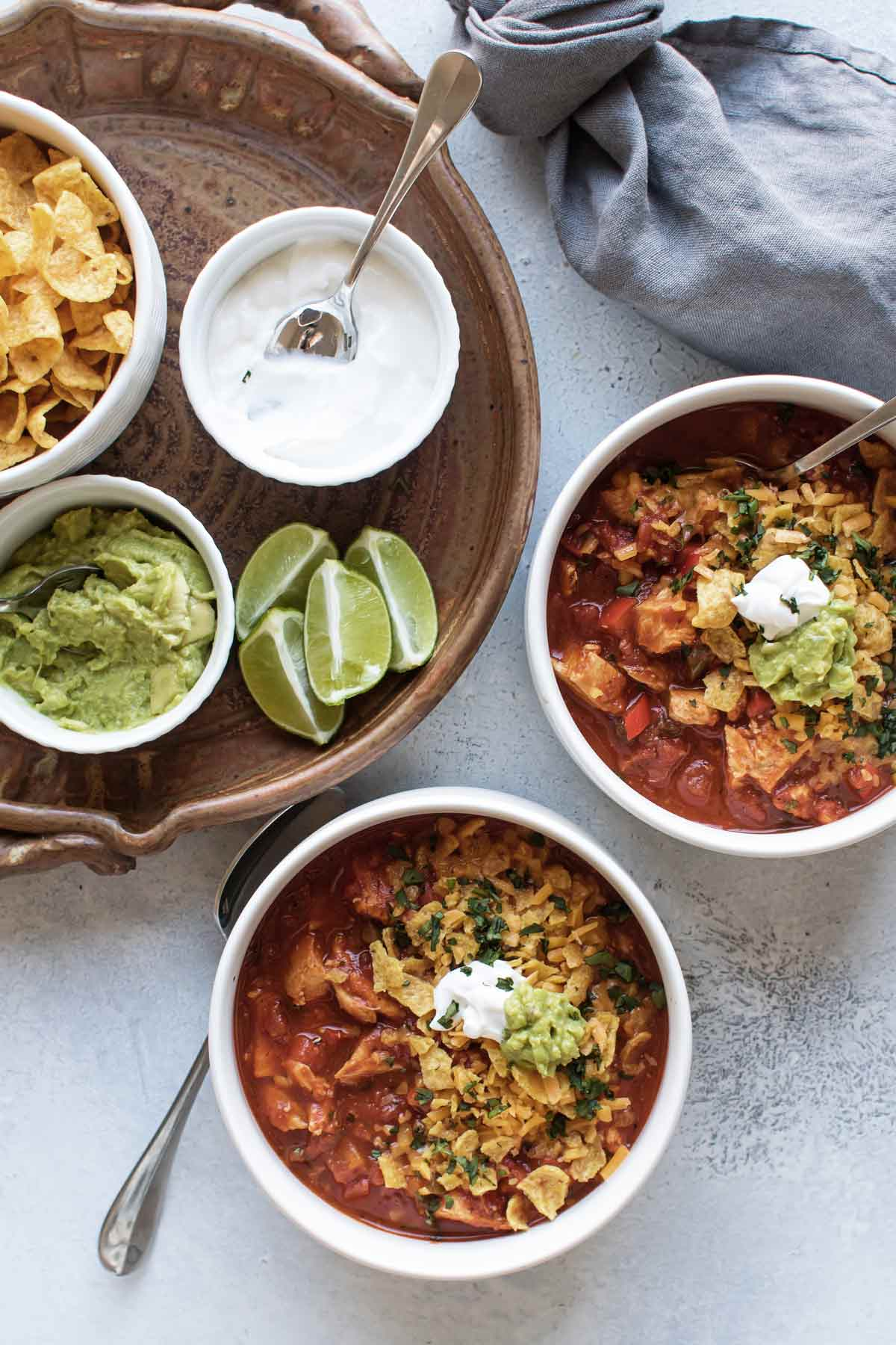 overhead shot of two bowls of chili with toppings on the side