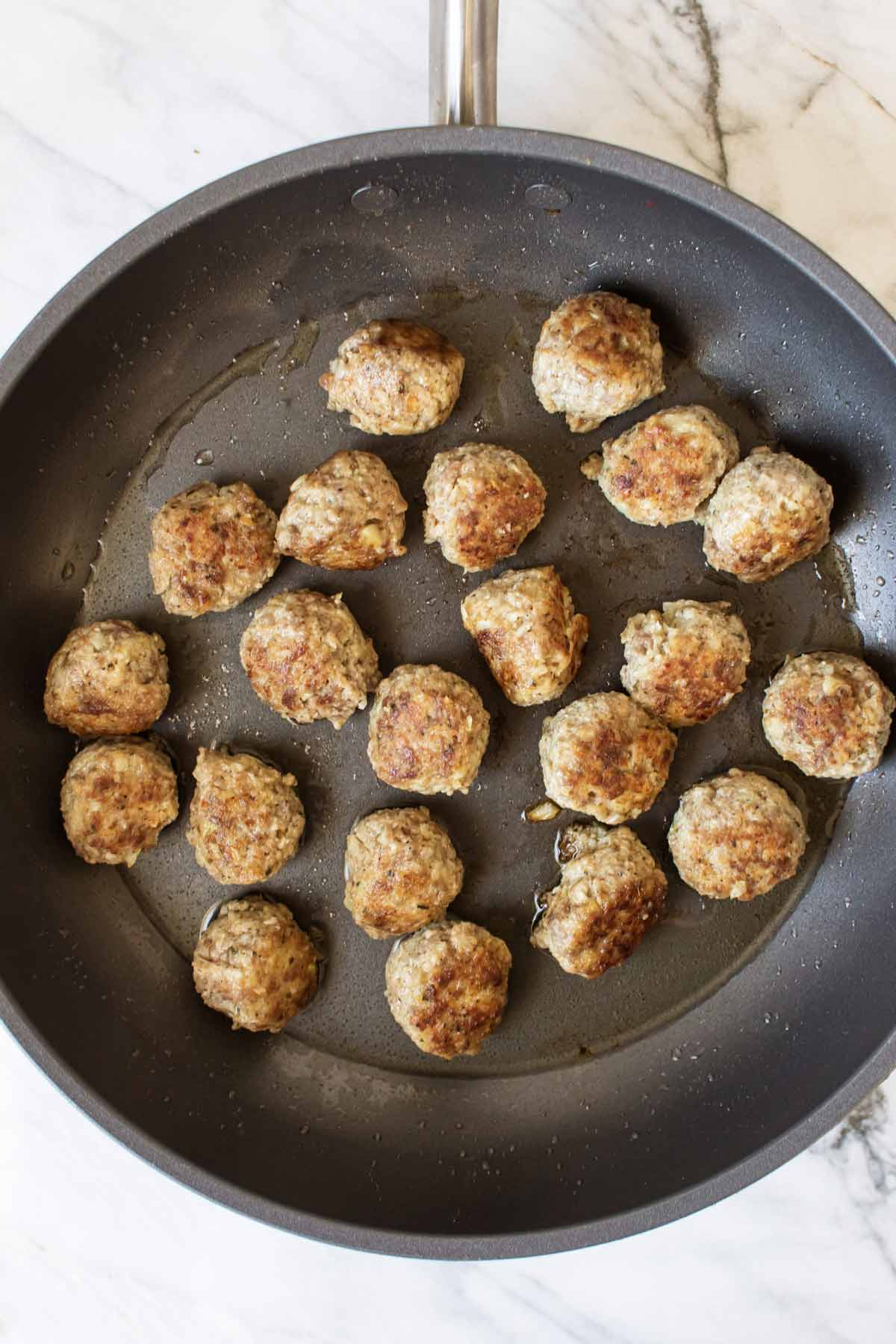 meatballs browning in a pan
