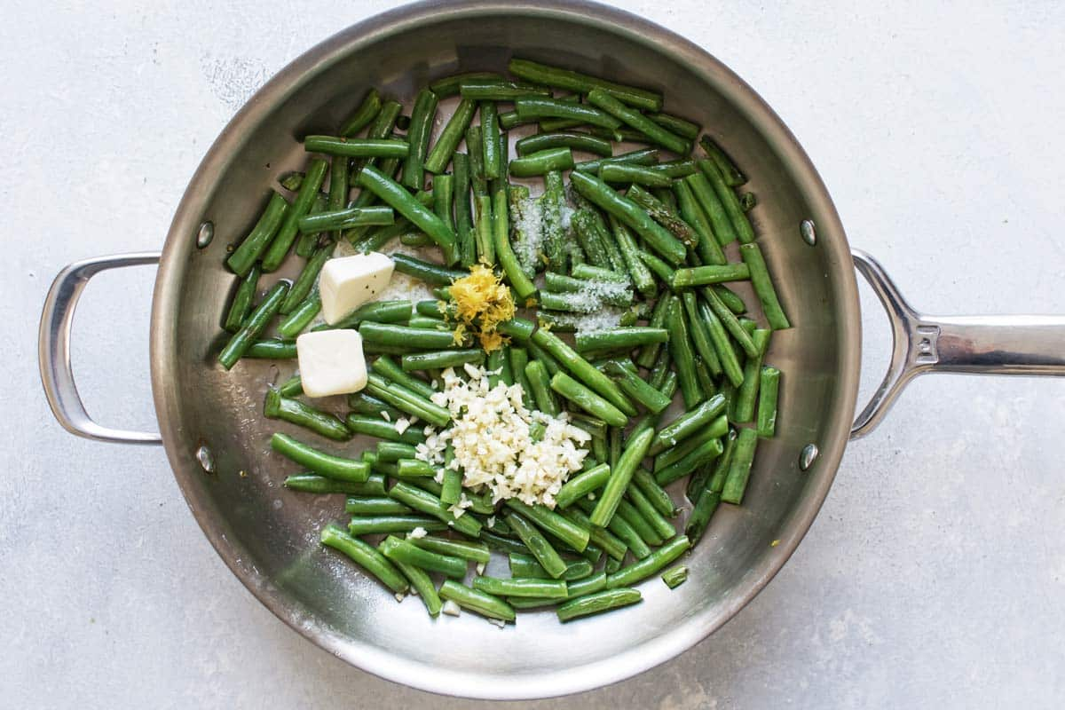 sauteed green beans in a skillet with butter, garlic, lemon zest, and salt.