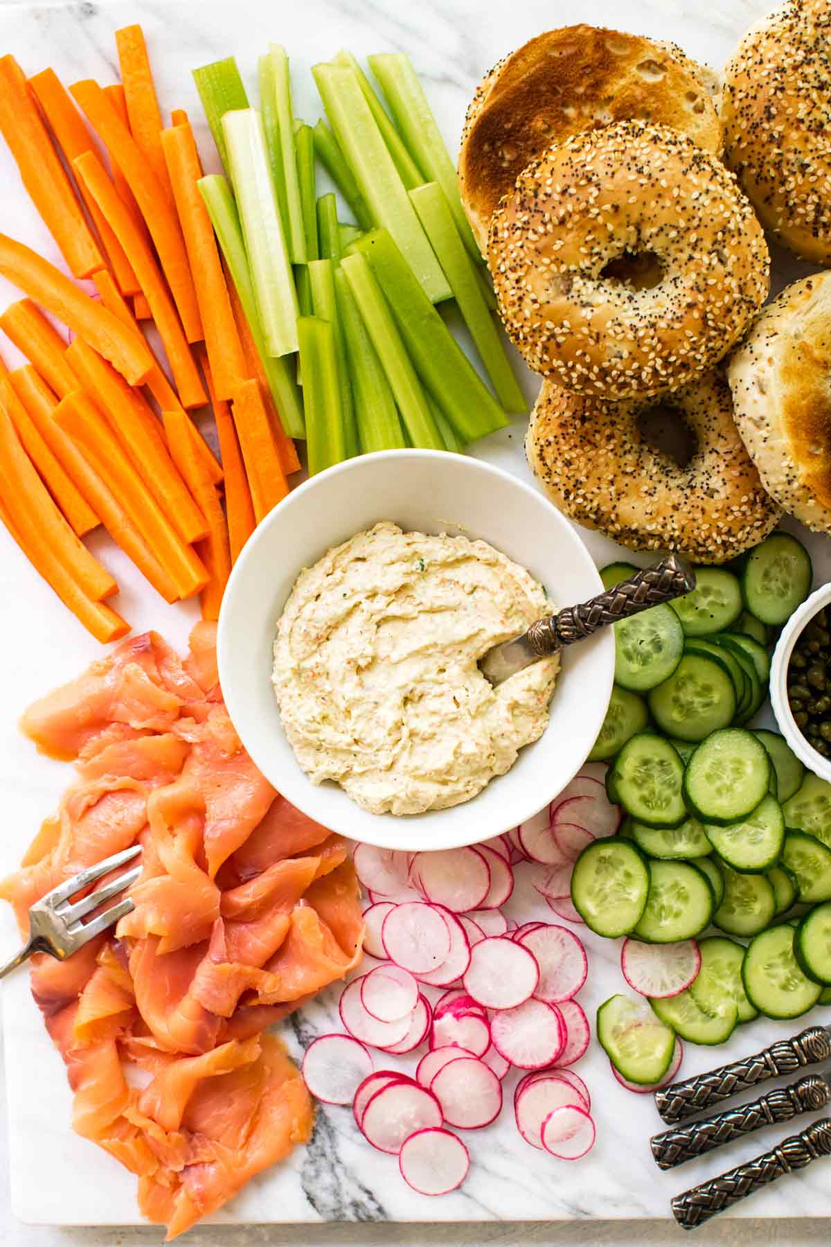 overhead shot of a platter with vegetable cream cheese, bagles, and vegetables
