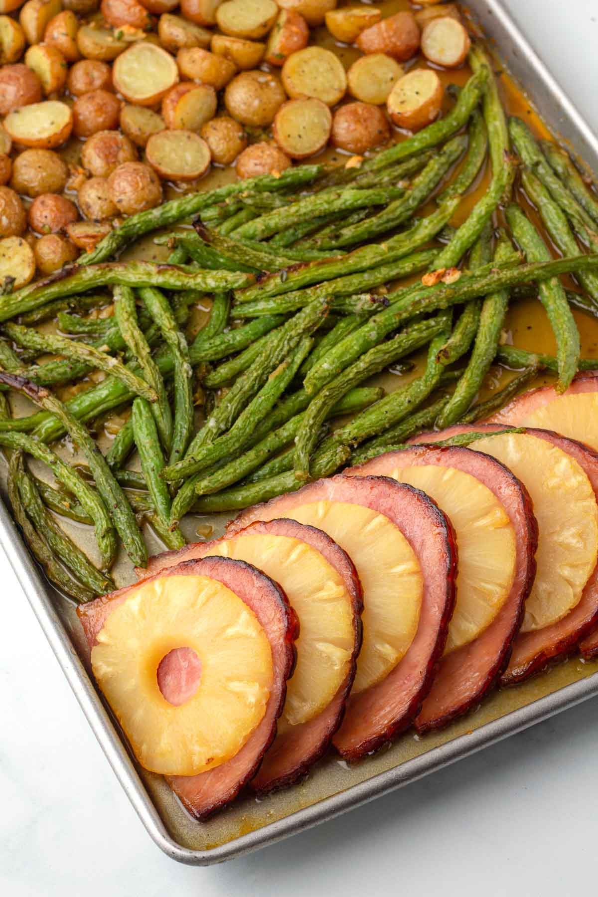 potatoes, green beans, pineapple, and ham slices on a sheet pan.