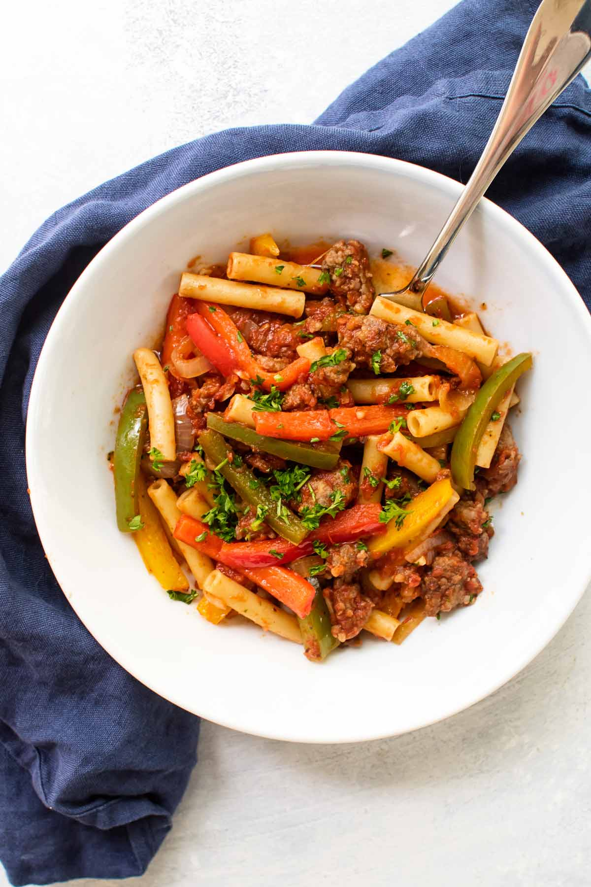 a bowl of pasta with sausage and peppers.