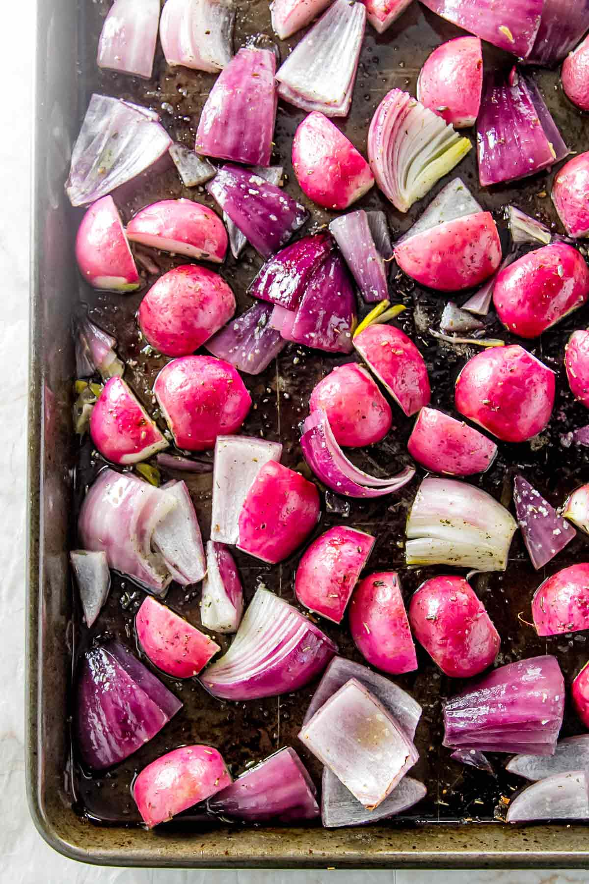 radishes and onions on a sheet pan after roasting.