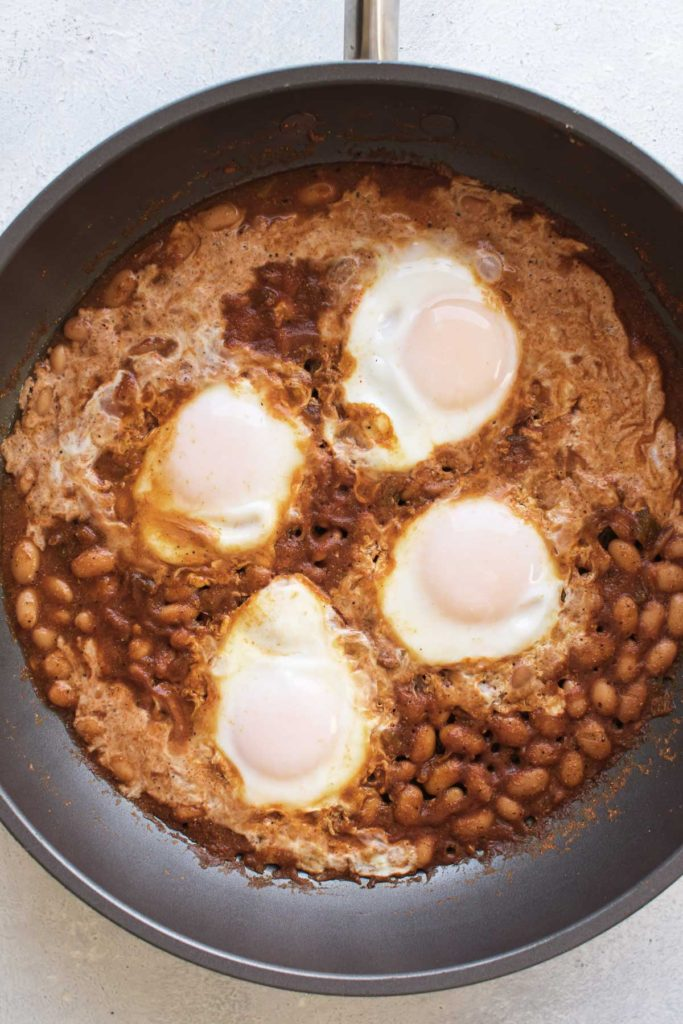 cooked eggs in the skillet with the beans.