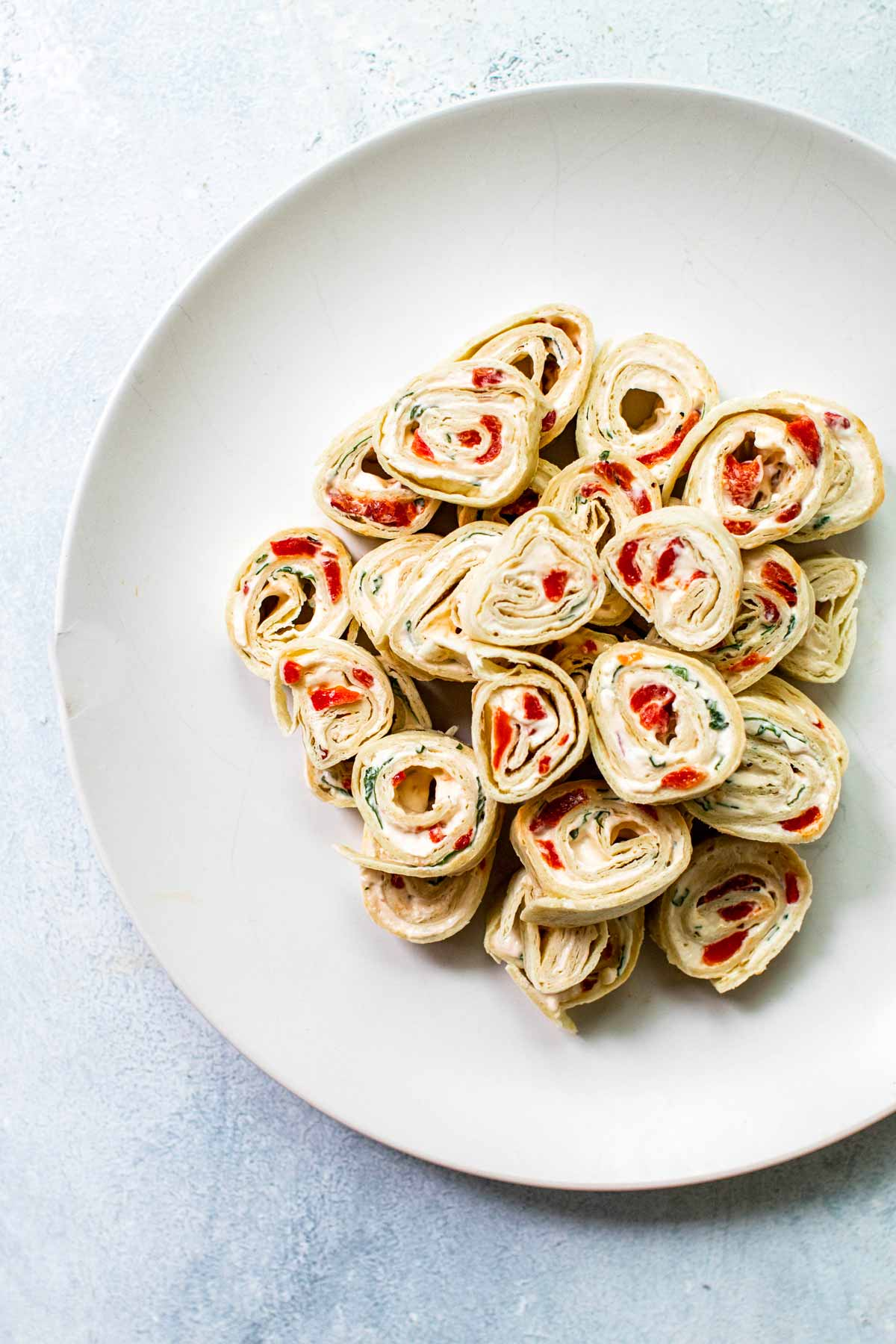 a stack of tortilla pinwheels on a white plate.