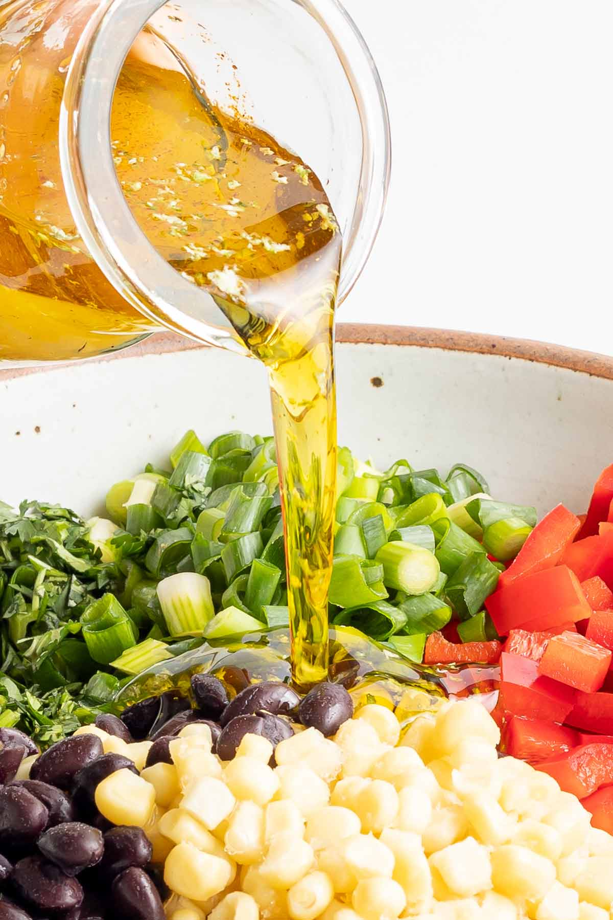 dressing being poured on the salad.
